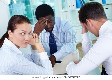 Portrait of sad business team sitting in office