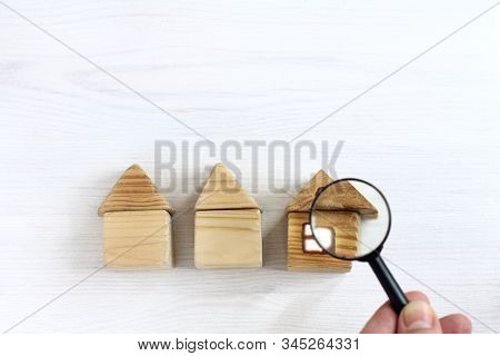 Three Houses To Choose From And A Hand With A Magnifying Glass. Careful Inspection Of Real Estate
