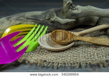 Rustic Wooden Utensils In A Kitchen Still Life With Two Spoons And Colorful Plastic Forks Over A Wea