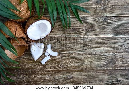 Coconut. Whole Coconut, Shell, Coconut Flakes And Green Leaves On A Wooden Background. Big Nut. Trop