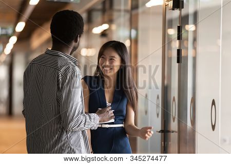 Smiling Millennial Multiracial Colleagues Talk In Office Hallway