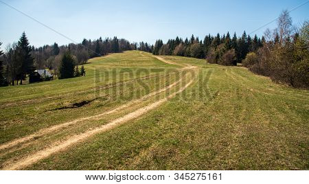 Springtime Mountain Meadow With Dirty Road, Trees Around, Isolated House And Clear Sky In Javorniky