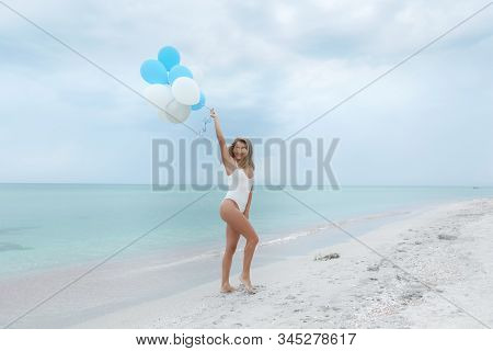 Leggy Sexy Woman 30-35 Years Old In A White Swimsuit With Balloons On The Background Of The Sea.