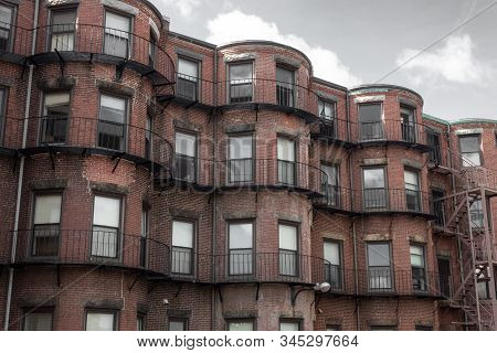 Run Down Brownstone Apartments Viewed From The Rear Before Gray Sky, Horizontal Aspect