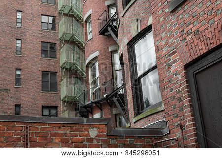 Layers Of Fire Escapes And Balconies On Rear Exterior Of Old Residential City Apartments, Horizontal