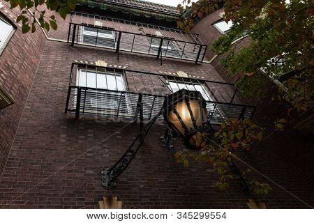 Entry Lamp Shaded By Trees On Exterior Of City Apartment Building, Horizontal Aspect