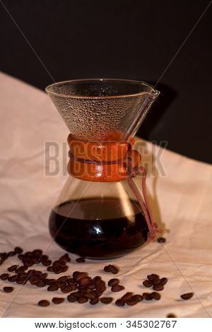 On Black Background And Dense Coarse Cloth Stands Glass Vessel For Brewing Strong And Invigorating C
