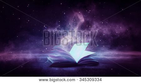 Open Book Magic. Dark Background Magic. An Open Book On A Wooden Table Under The Night Sky Against A