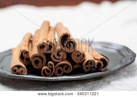 Winter Food Ingredient, Dried Aromatic Cinnamon Sticks On Tin Plate