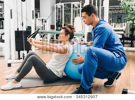 Kinesiologist Helps A Woman Do Exercises To Strengthen Her Back Muscles. Treatment Of Back Pain With