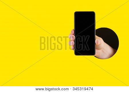 Hand Holds Black Cellphone Through A Hole In A Yellow Paper Background. Template For Design. Close U