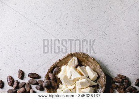 Chopped Pieces Of Raw Organic Cocoa Butter In Craft Ceramic Plate And Cocoa Beans Over Grey Spotted