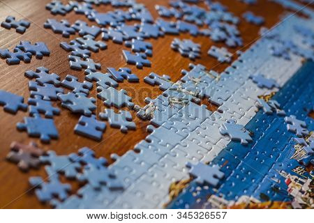 Partially Solved Jigsaw Puzzle With Scattered Puzzle Pieces On The Table