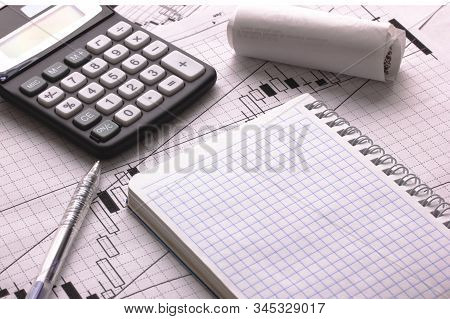 On The Table Are Calculator Pen Check Notepad And Financial Graphics
