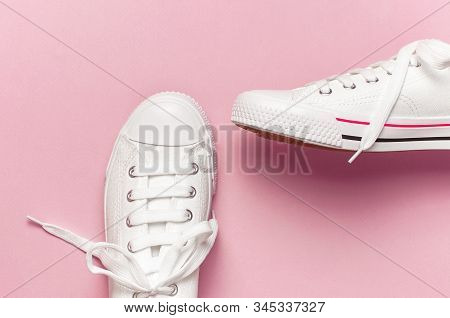 White Female Fashion Sneakers On Pink Background. Flat Lay, Top View, Copy Space. Women's Shoes. Sty