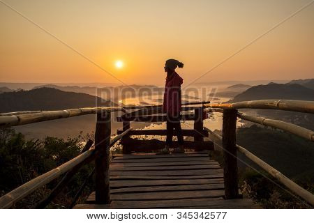 Woman Enjoying Watch The Sunrise On The Mekong River And Standing On The Wooden Bridge Alone Her