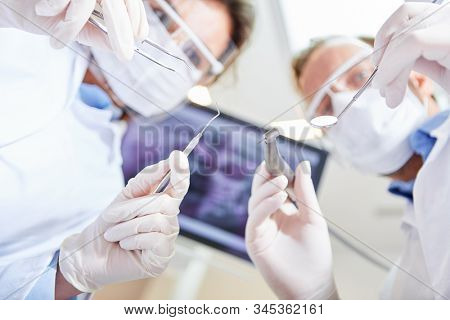 Two dentists as a team in an emergency operation in the oral surgery of a dental clinic