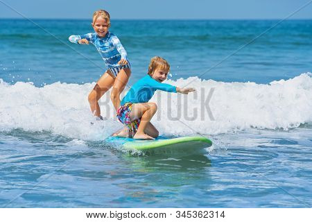 Happy Baby Boy And Girl - Young Surfers Ride With Fun On One Surfboard. Active Family Lifestyle, Kid