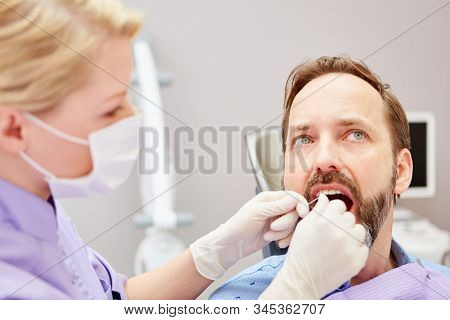 Dental assistant makes flossing a professional teeth cleaning in a patient