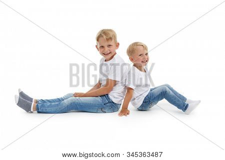 Friendly family. Older brother and younger boy are sitting with backs to each other isolated on a white background. Happy siblings. Two little brothers. Concept of people and family,