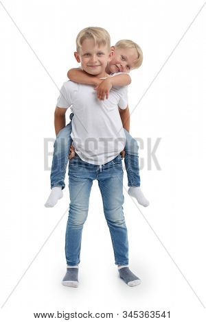 Friendly family. Older brother is holding behind the back younger boy, standing isolated on a white background. Happy siblings. Two little brothers. Concept of people and family,