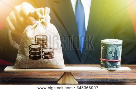 A Man Puts A Money Bag On The Scales Opposite To The Dollar. Exchange Rate, Comparison Of Economic I