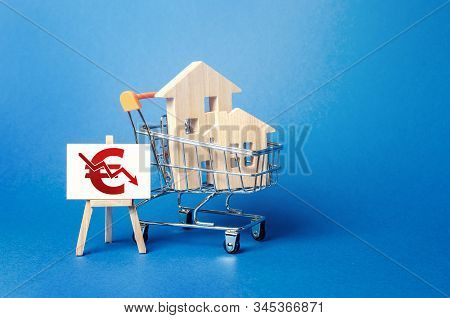 Wooden Houses In A Shopping Cart And An Easel With A Red Euro Arrow Down Chart. Low Sales. Value Cos