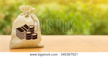 Money Bag On Nature Background. Economics, Salary. Business And Industry, Economic Processes. Financ