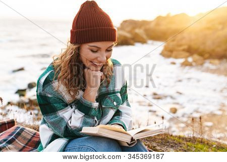Image of caucasian joyful woman reading book and smiling while sitting on blanket by seaside