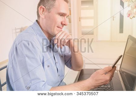 Hearing impaired man working with laptop and mobile phone at home or office