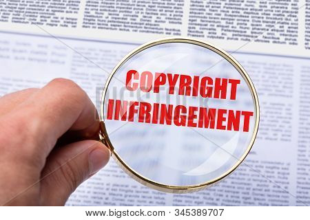 Person Holding Magnifying Glass Over Copyright Infringement Word