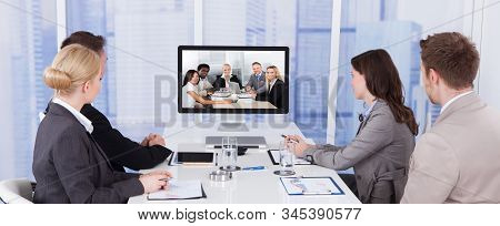Business People In Video Conference At Meeting Table
