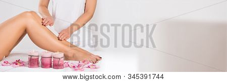 Beautician Waxing Woman's Leg At Salon