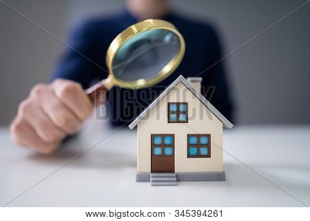 Person Hands With Magnifying Glass And Model House