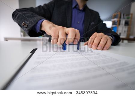 Close-up Of Person Hands Using Stamper On Document