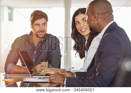 Multiethnic business partners discussing documents and ideas at meeting room. African businessman working with colleagues. Executive man planning work at meeting with businesswoman and associate.