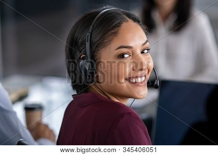 Portrait of smiling young businesswoman wearing headset in office. Portrait of a customer service agent looking at camera. Happy telephone operator latin girl with headset working at computer.