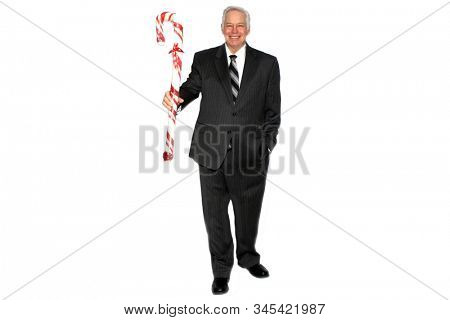 Christmas. A business man holds a Giant Red and White Candy Cane. Isolated on white. Room for text. Clipping Path. People world wide celebrate Christmas each year. Candy Canes are a part of Christmas.