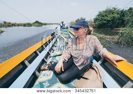 Nyaungshwe, Myanmar - April 2019: Tourist Woman Transporting Bicycle In Traditional Burmese Wooden B