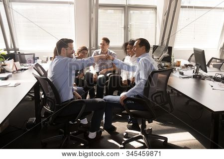 Male Employees Give Fists Bump Engaged In Office Training