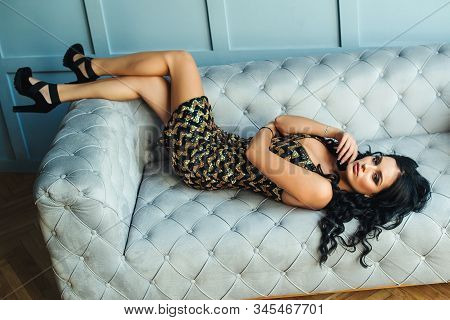 Fashionable Sensual Brunette Woman Lies On Sofa, Top View. Sexy Girl With Perfect Body. Woman In Fas