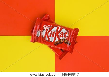 Kit Kat Chocolate Bars In Red Wrapping Lies On Yellow And Red Background. Kit Kat Created By Rowntre