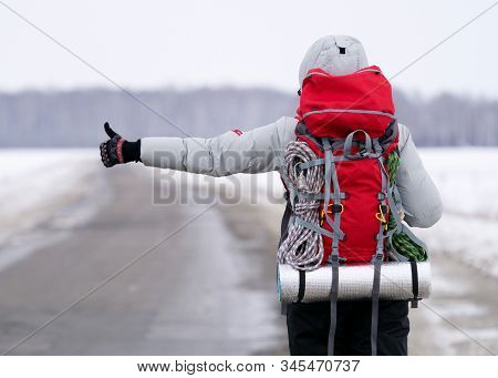 Travel Hitch Hiker Holding Thumb Up On Secondary Road To Share A Ride. Winter Time, Back View, Selec