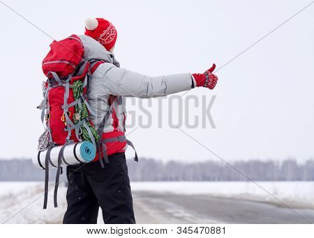 Hitch Hiker In Winter Sportswear With Big Red Backpack Holding Thumb Up On Snow Countryside Road To