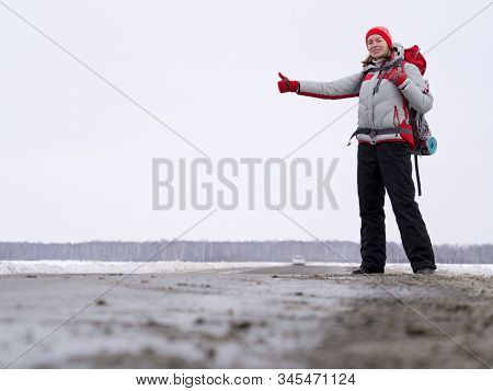 Woman Hitch Hiker Try To Catch A Car Showing Thumb Up On A Road To Share A Ride. Winter Time, Front