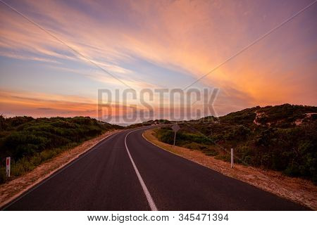 Scenic Road Winding Into The Distance Near The Ocean At Beautiful Sunset