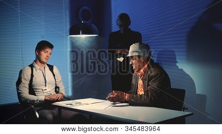 Medium Shot Of Police Detective Giving Black Murder Criminal A Document To Sign A Confession About T