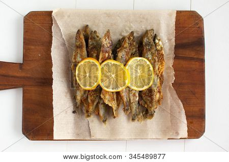 Fried Capelin With Lemon On Baking Paper On A White Background. Top View