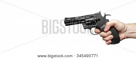 Male Hand With A Black Revolver Ready To Shoot. The Finger Presses The Trigger. Close-up. Isolate On