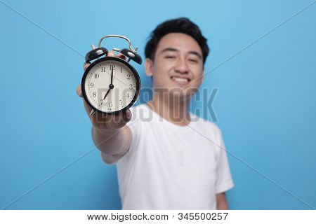 Young Asian Man Wearing Shite Shirt Shows Time On Clock With A Happy Expression, Time Management. Ha
